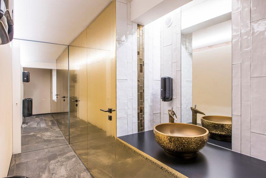 Monochroom zwart en goud accenten moderne badkamer met spanplaofnds en spanwanden en led verlichting.