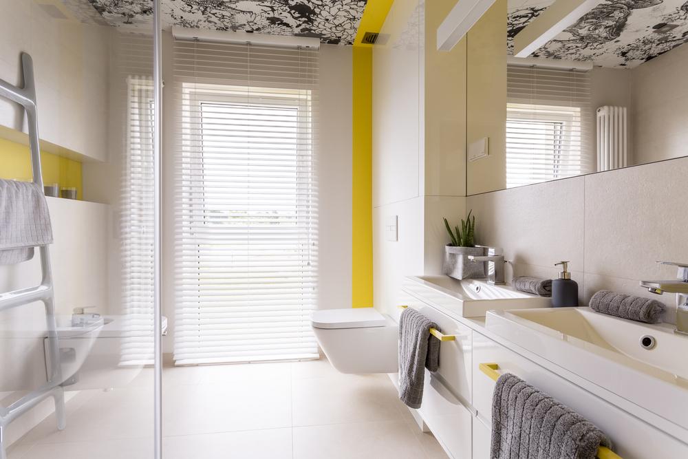 Moderne badkamer design met statement printwand. Gele accentmuur.