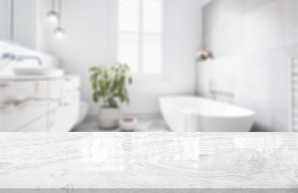 Witte moderne badkamer met marmeren wastafel en bad. Witte spanplafonds en witte spanwanden.