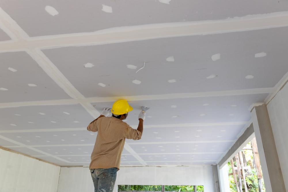 Gyproc plafond. Man bevestigd Gyproc platen aan het plafond en pleistert de naden en gaten. Plafond renoveren. Plafond renovatie
