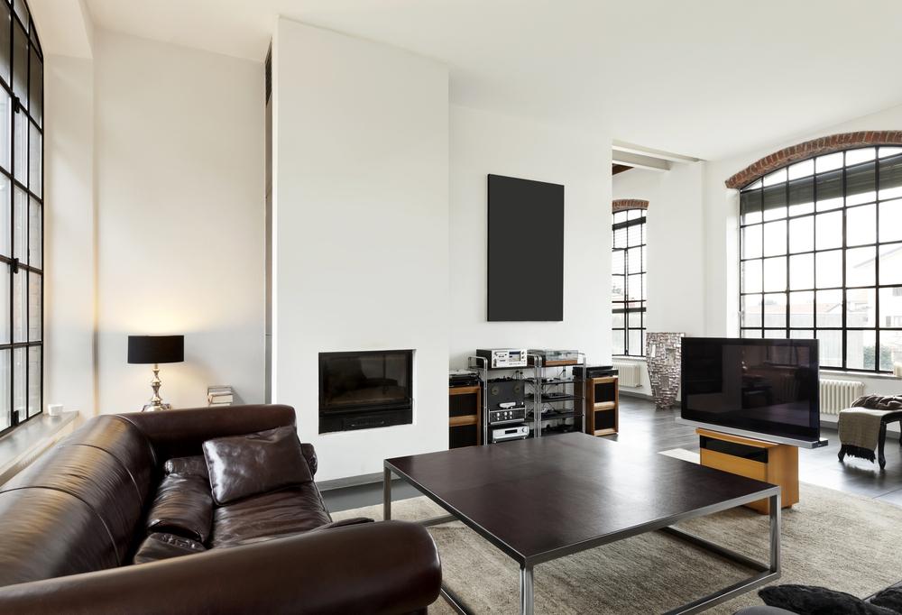 Moderne woonkamer met een spanplafond en bruine lederen zeten. Spanwand met akoestische eigenschappen.