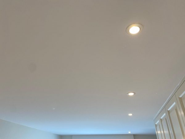 afgewerkt eindresultaat spanplafond met LED verlichting in grote slaapkamer
