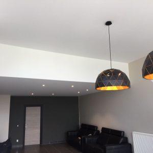 spanplafond en verlaagd spanplafond met hangverlichting in een moderne studio