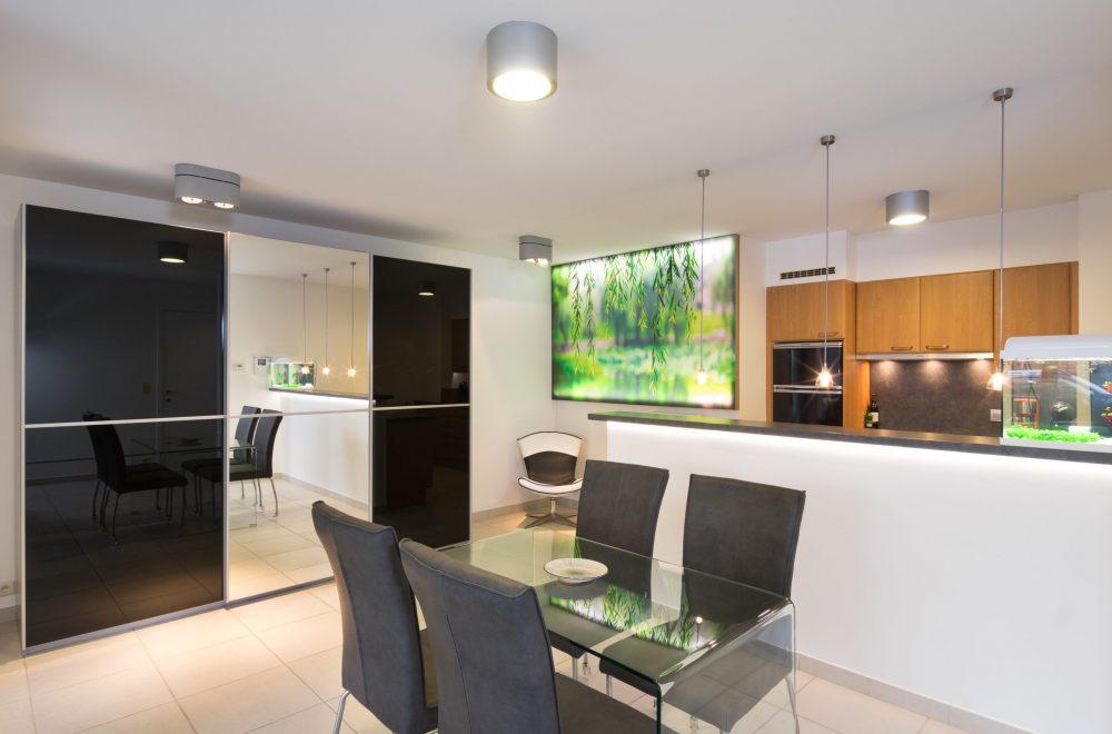 spanplafond met opbouwverlichting en hangarmaturen in een moderne open keuken amerikaans model