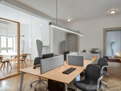 spanplafonds met ronde spots en hang armatuur in een communucatie kantoor