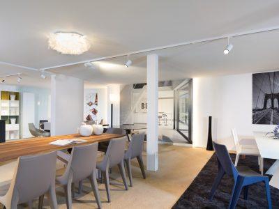 witte spanplafond met railverlichting in moderne showroom